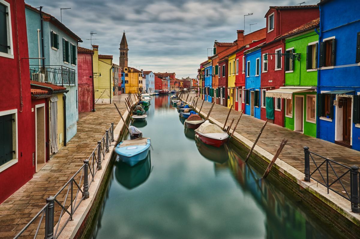 Canal avec des bateaux avec les maisons colorées de Burano